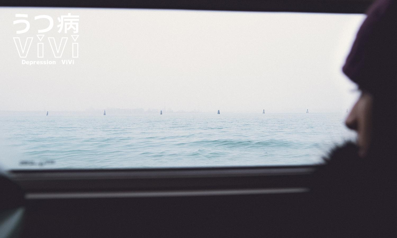 電車の窓から海を見る女性
