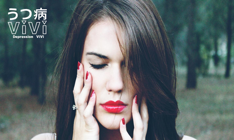 目を閉じ両手を頬にあてる赤い口紅とネイルの女性