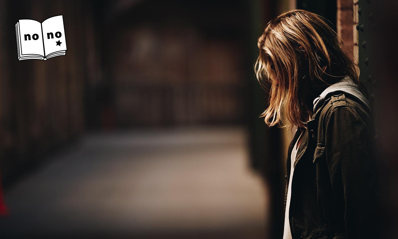 扉の前でうつむく金髪の女性